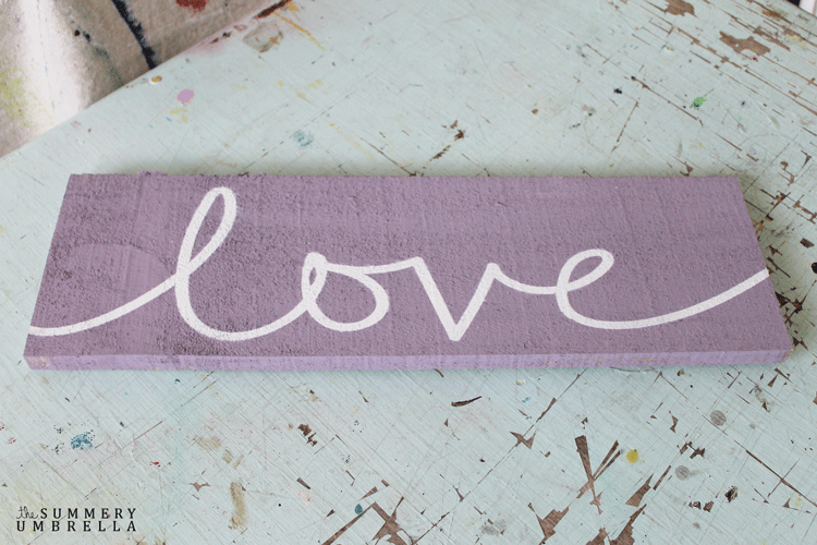 A distressed wood sign with the word love on it