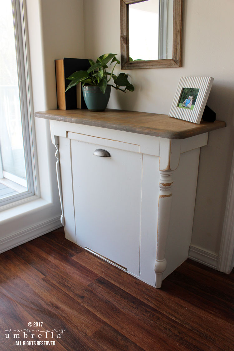 Ever wondered what you could do with that old table you have lying around? Well, you could give it a makeover and turn it into a DIY wood tilt out trash can for your kitchen! #DIY #kitchenorganization #TheSummeryUmbrella #LZCathcart