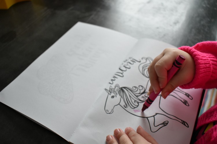 kids coloring on DIY coloring book with unicorn