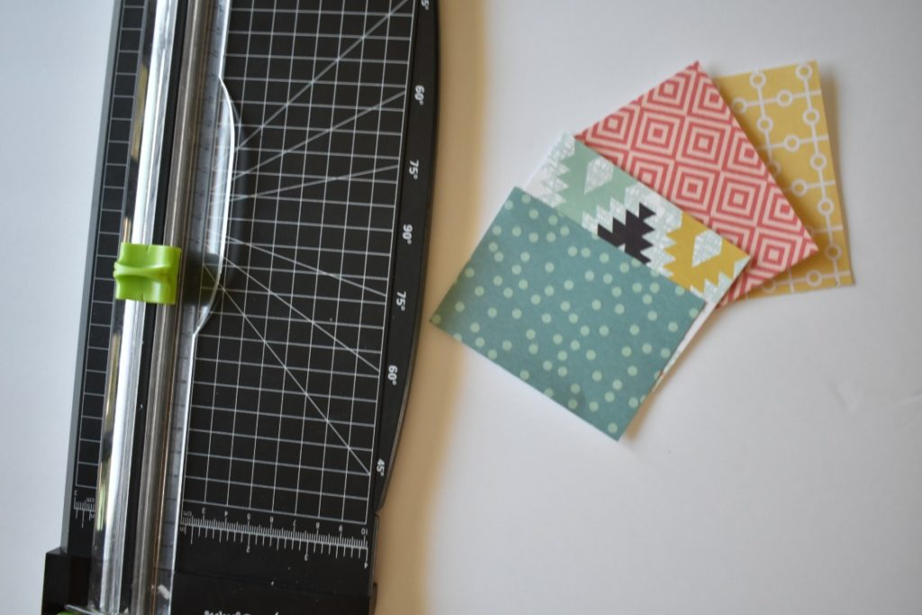 a paper trimmer is being used to cut rectangles out of scrapbook paper
