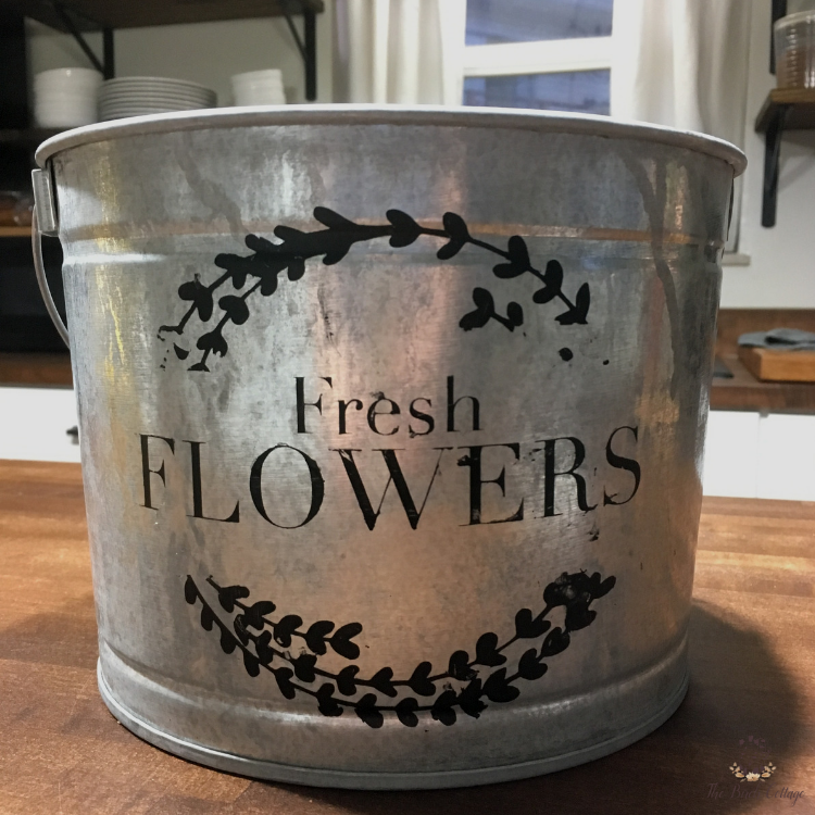 flower market sign stenciled on a galvanized bucket