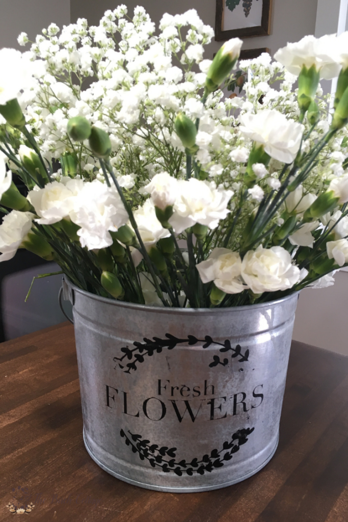 Learn how to stencil a beautiful DIY French flower market galvanized metal bucket using paint, a SVG file and a cutting machine with ideas on how to use it in your home decor. #farmhouse #farmhousedecor #TheSummeryUmbrella #LZCathcart