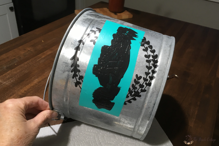 painting a flower market stencil onto a galvanized bucket